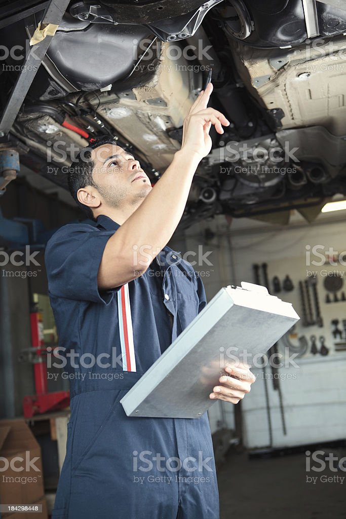 Mechanic checking a car with clipboard stock photo