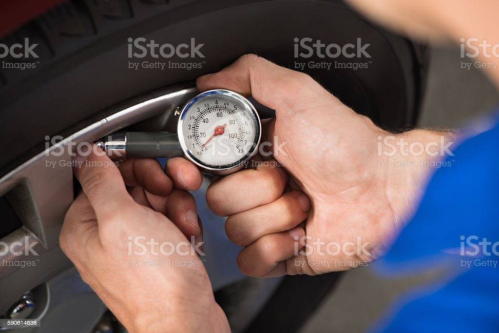 Mechanic Checking Air Pressure Level In Car Tire stock photo