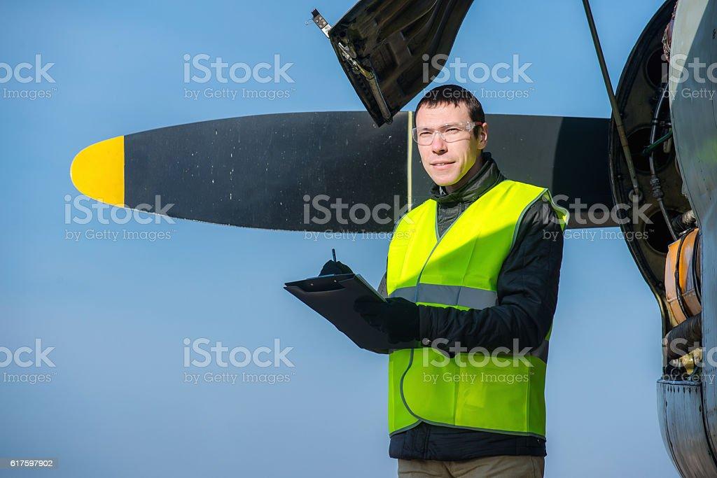 Mechanic checking airplane's engine stock photo