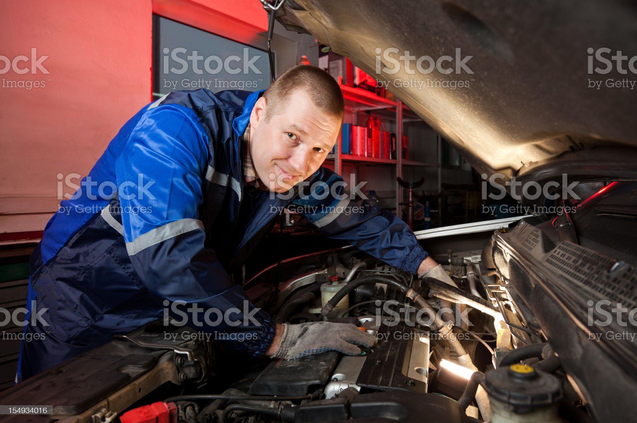 Mechanic checking engine under the hood royalty-free stock photo