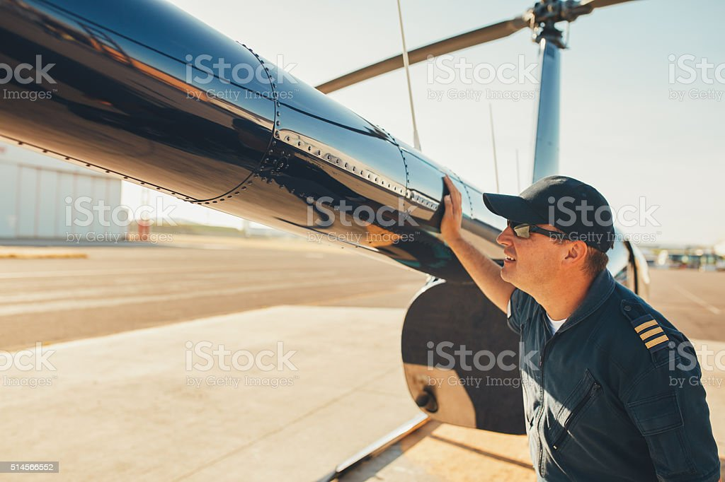 Mechanic checking helicopter before take off. stock photo