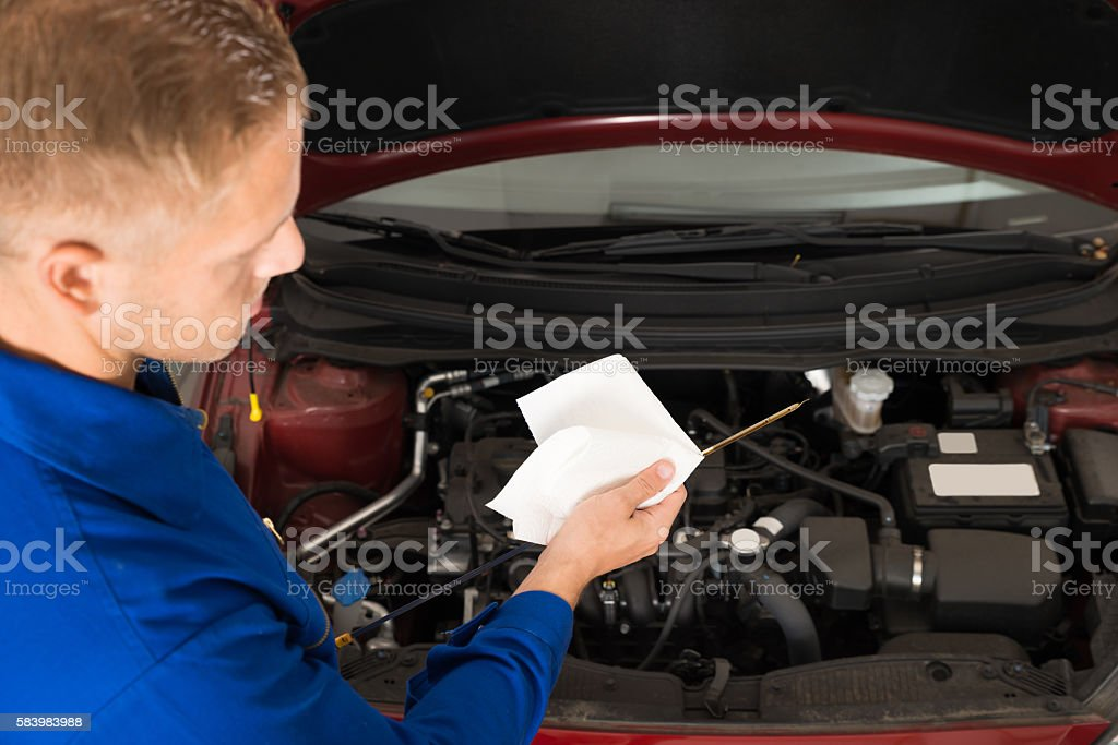 Mechanic Checking Oil Level In Car Engine stock photo