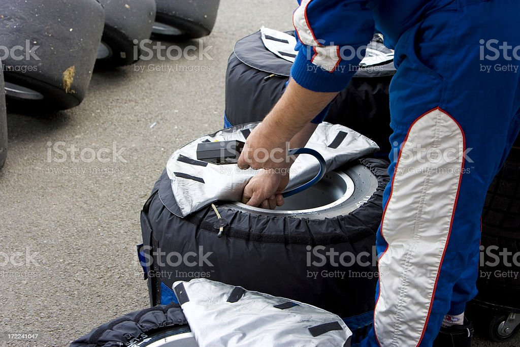 Mechanic checking racing tyres stock photo