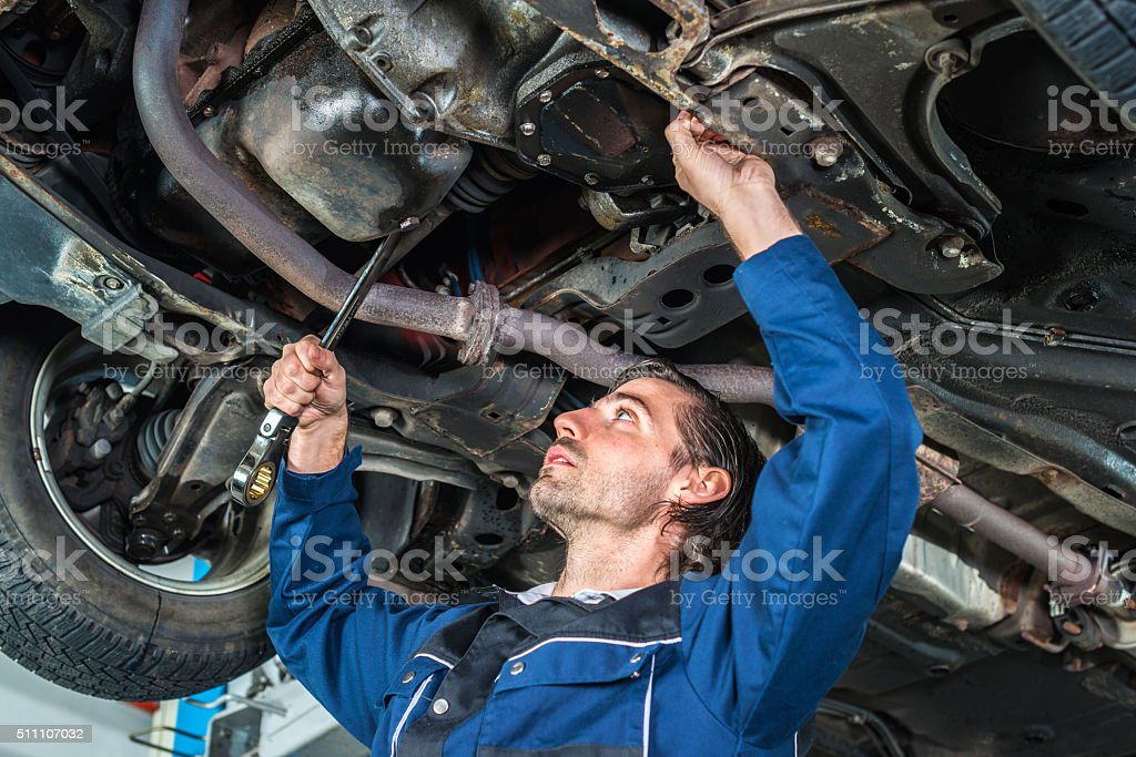 Mechanic checking the condition of a lifted car stock photo
