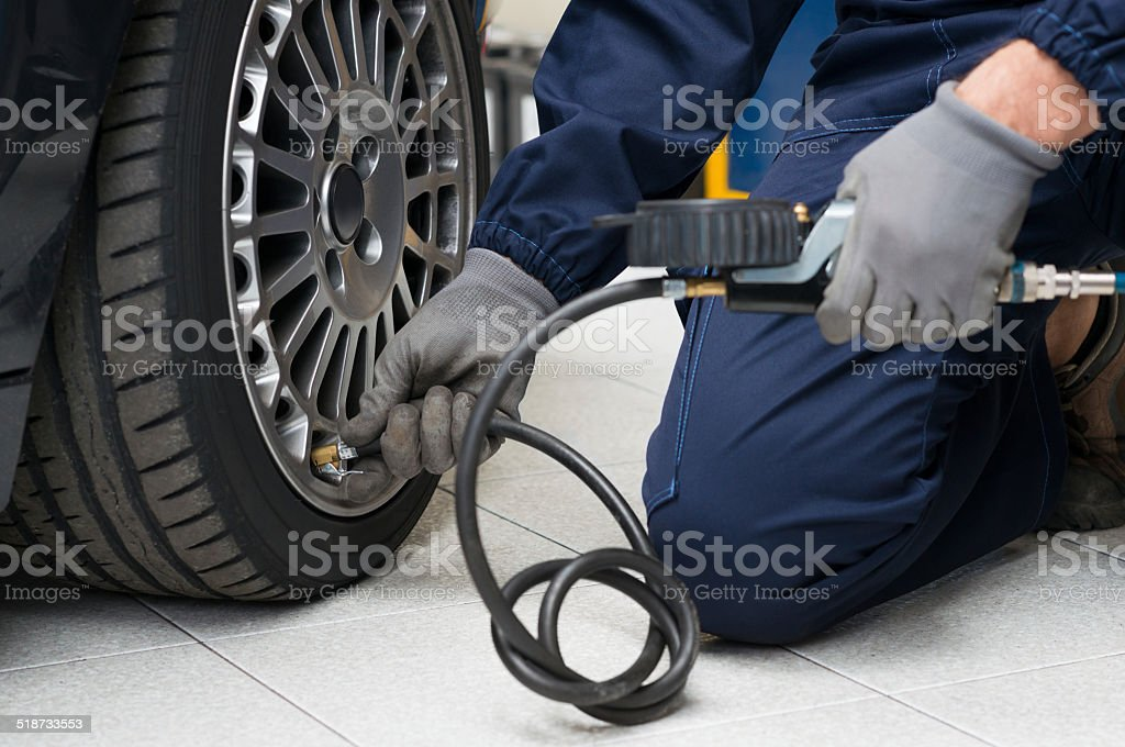 Mechanic Checking Tyre Pressure With Gauge stock photo