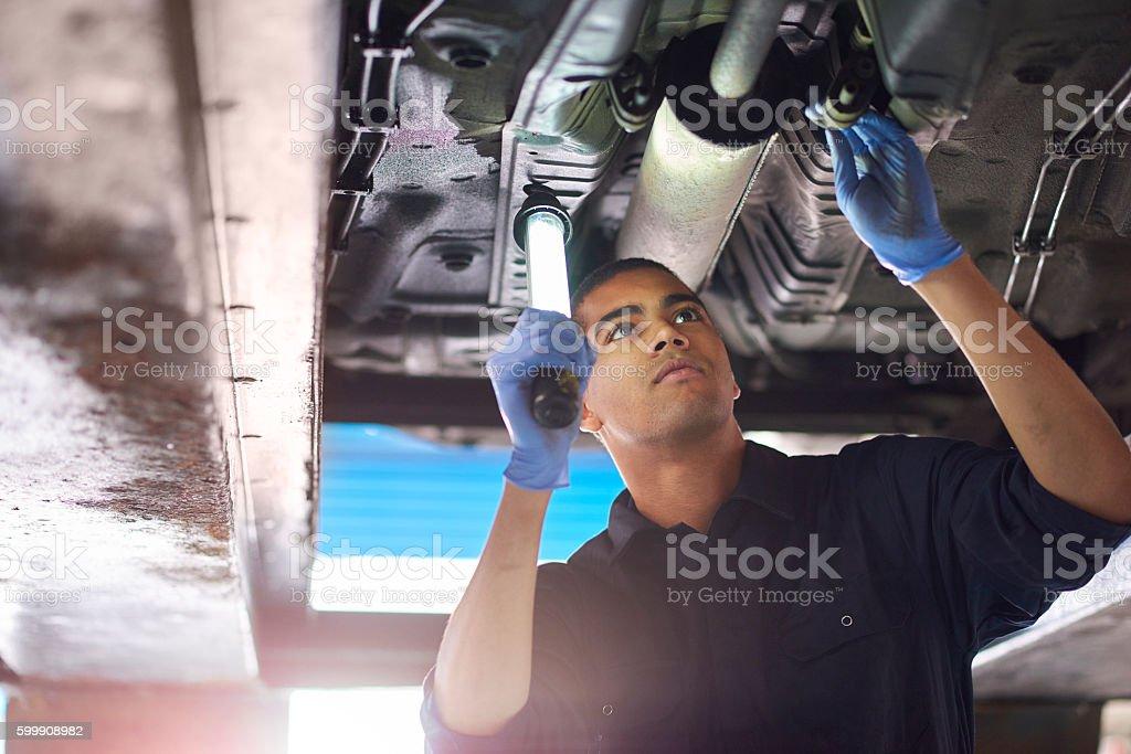 Mechanic checks exhaust stock photo