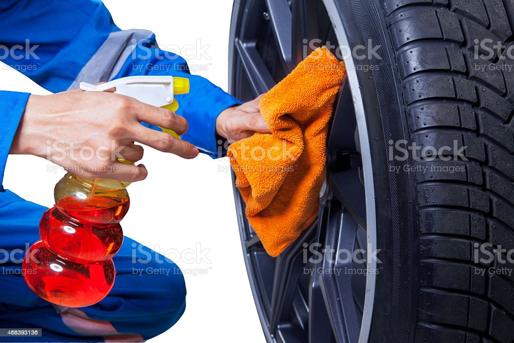 Mechanic cleaning a tire rim stock photo