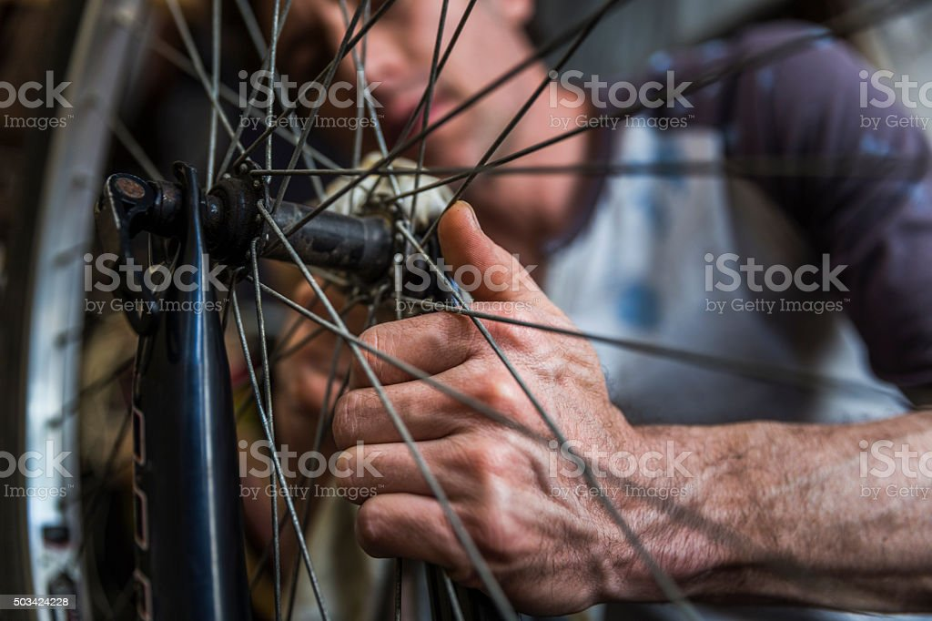 Mechanic cleaning bicycle nut in workshop stock photo