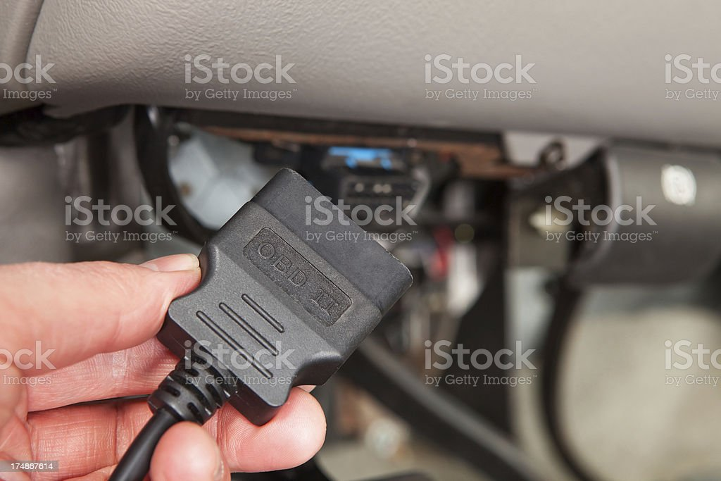 Mechanic Connecting OBD Scanner below SUV Dashboard stock photo