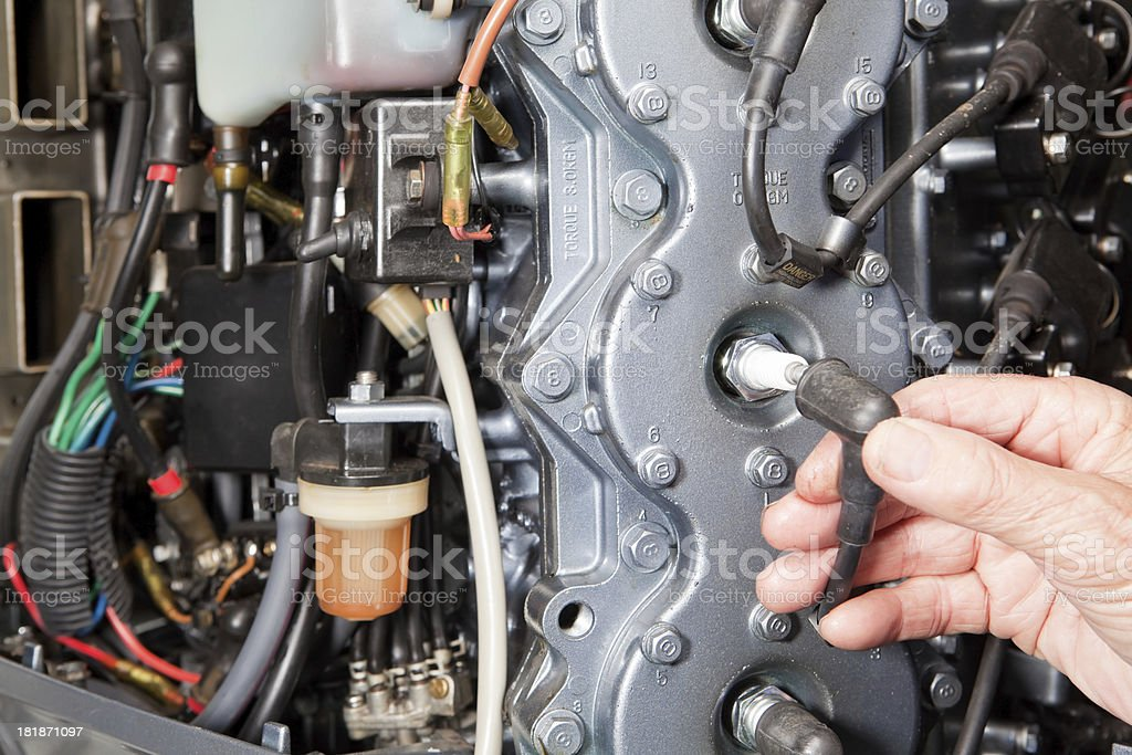 Mechanic Connecting Outboard Marine Engine Spark Plug Wire stock photo