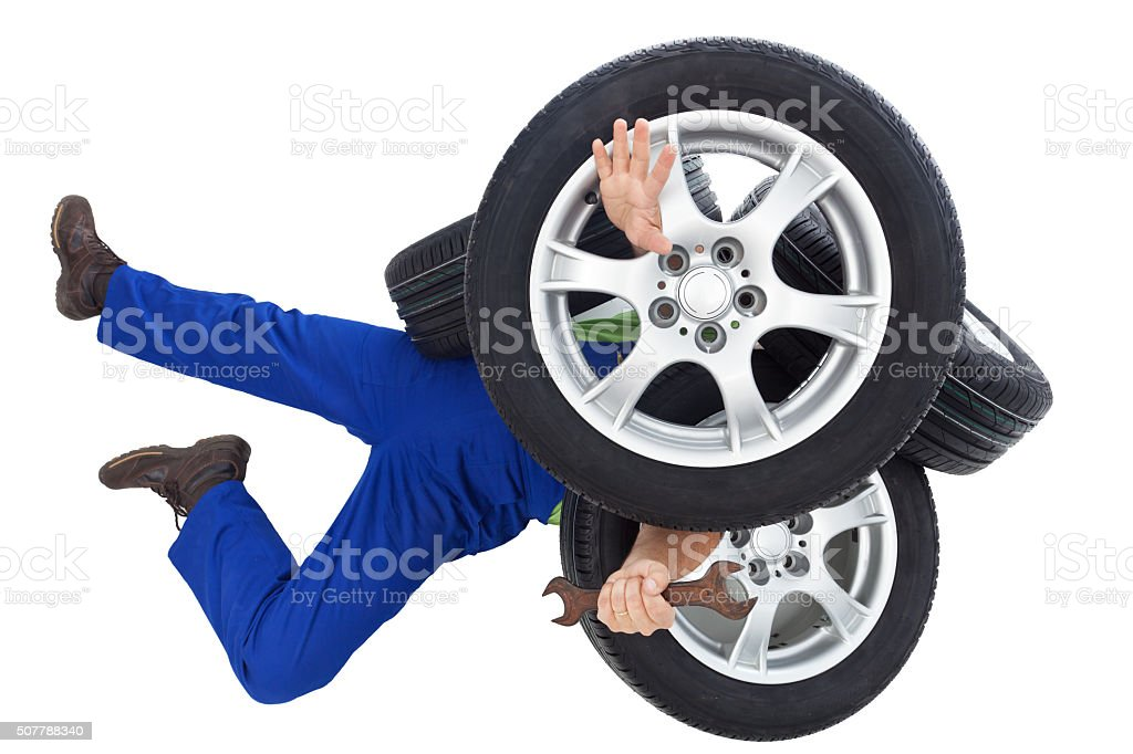 Mechanic covered by car tires stock photo