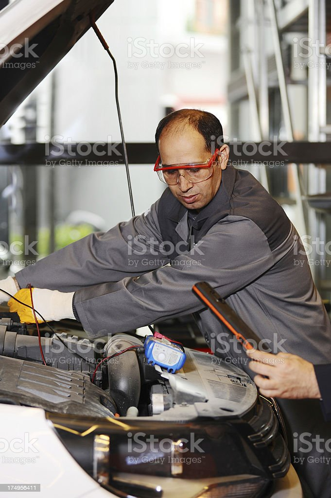 Mechanic diagnosing engine problem stock photo