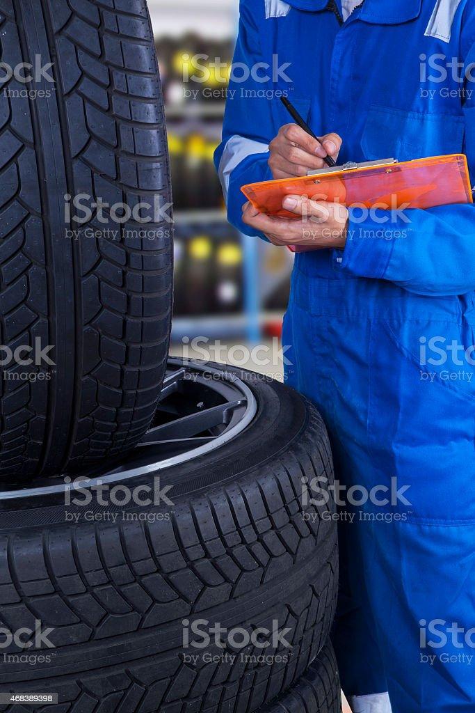 Mechanic examine the tires condition stock photo