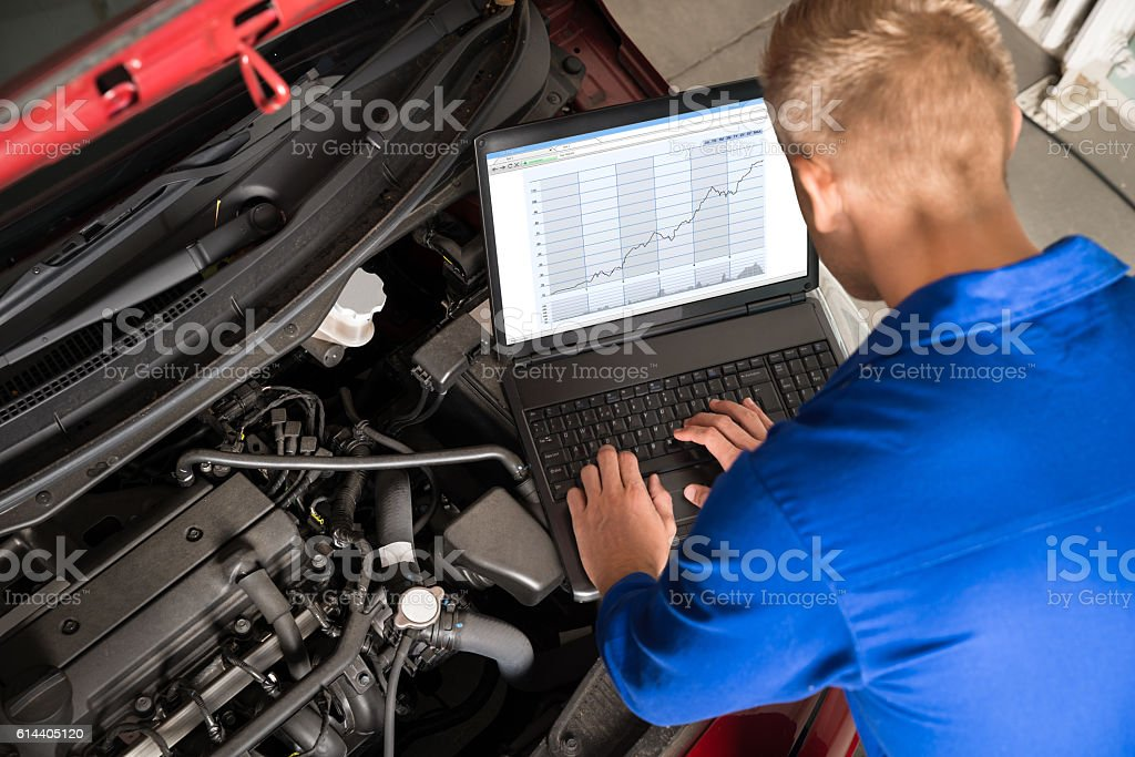 Mechanic Examining Car Engine With Help Of Laptop stock photo
