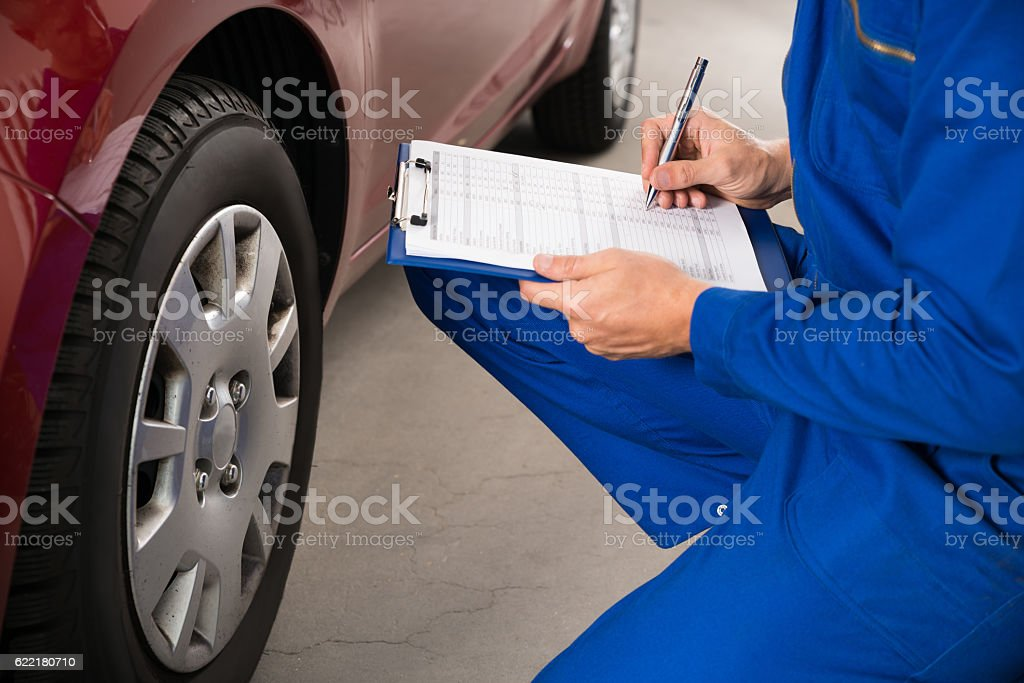 Mechanic Examining Car Wheel stock photo