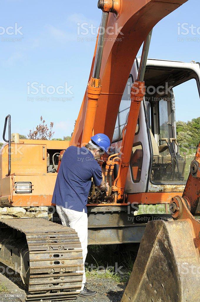 Mechanic Examining Excavator royalty-free stock photo