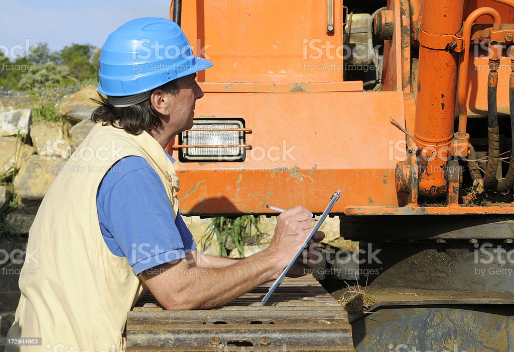 Mechanic Examining Tractor royalty-free stock photo