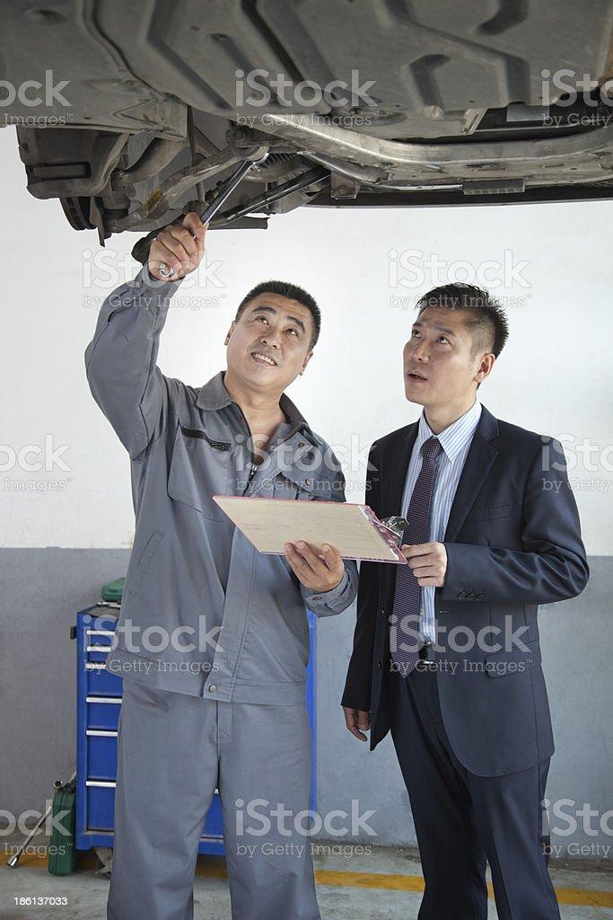 Mechanic Explaining to Businessman royalty-free stock photo