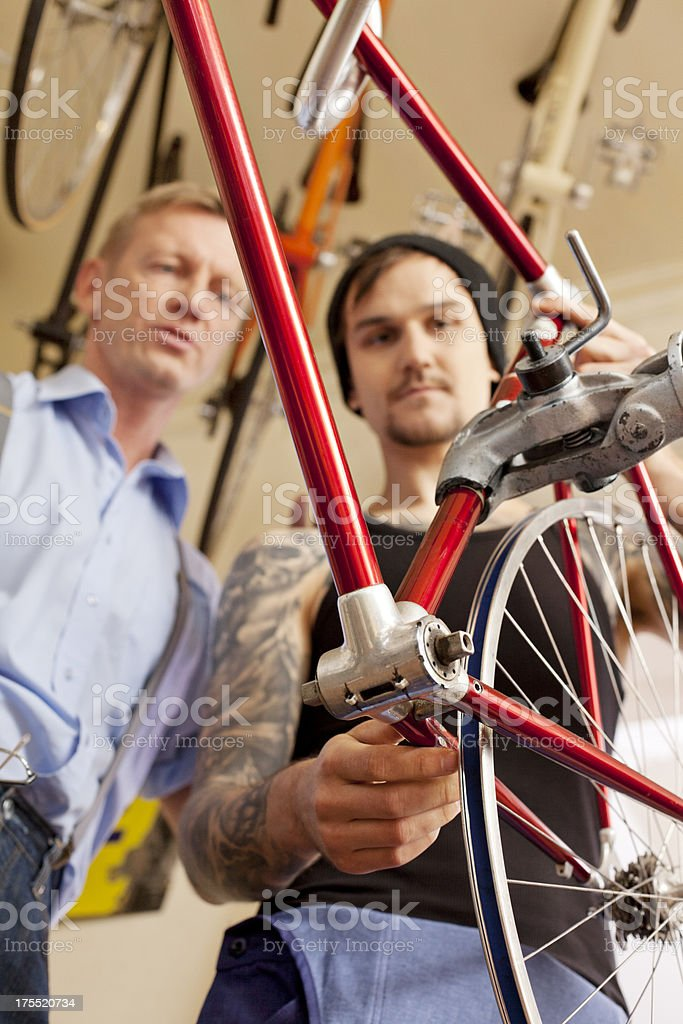 Mechanic fixing bike at bicycle shop stock photo