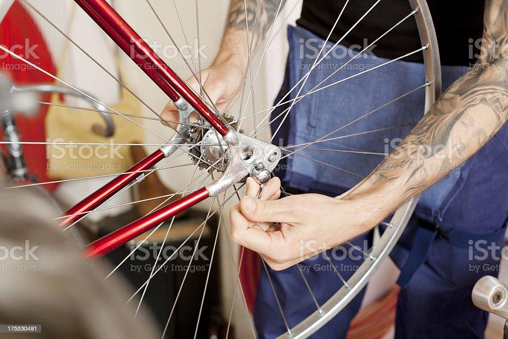 Mechanic fixing bike at bicycle shop royalty-free stock photo