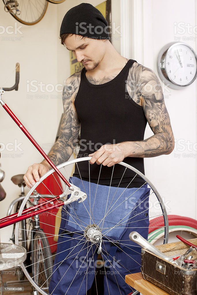 Mechanic fixing bike at bicycle shop royalty-free stock photo