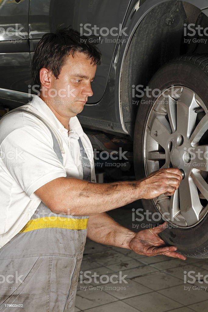 Mechanic fixing car tire royalty-free stock photo