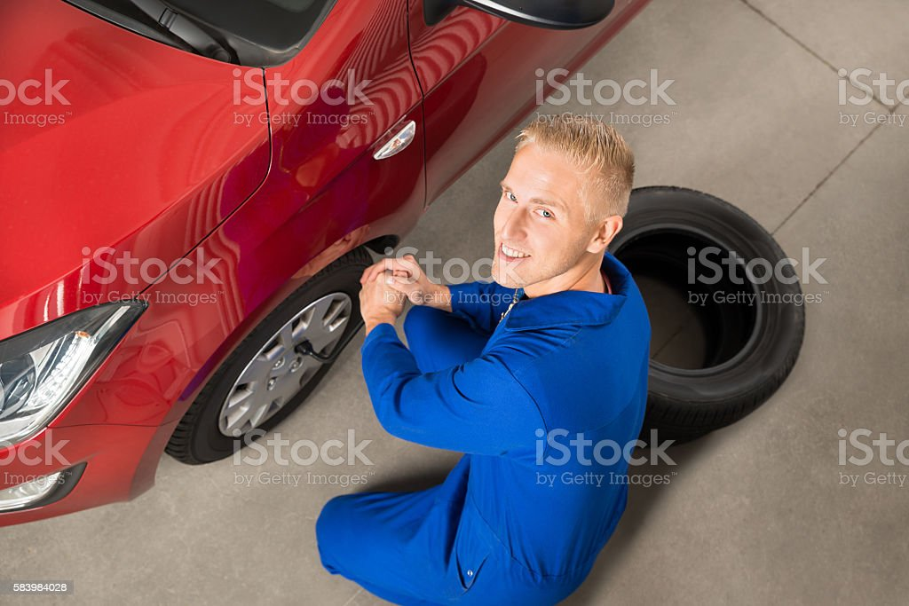 Mechanic Fixing Car Tire With Wrench stock photo