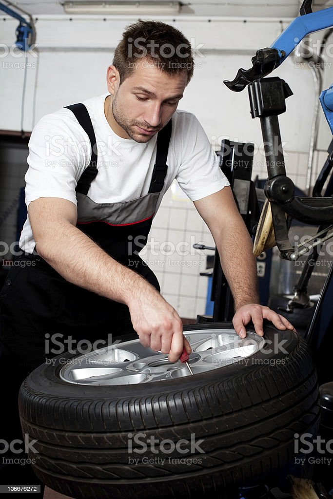 Mechanic fixing tyre in car service royalty-free stock photo