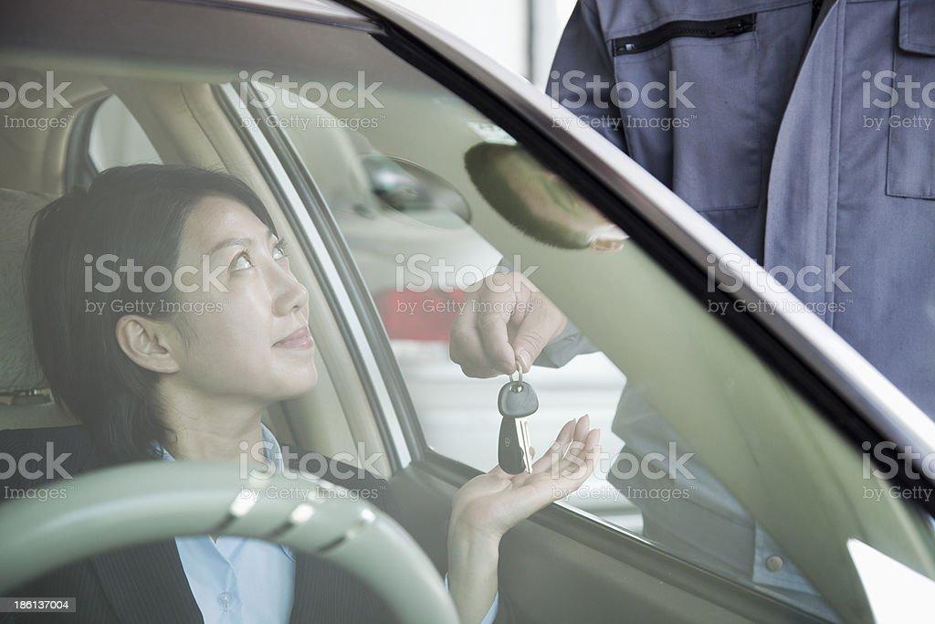 Mechanic Handing Keys to Businesswoman royalty-free stock photo