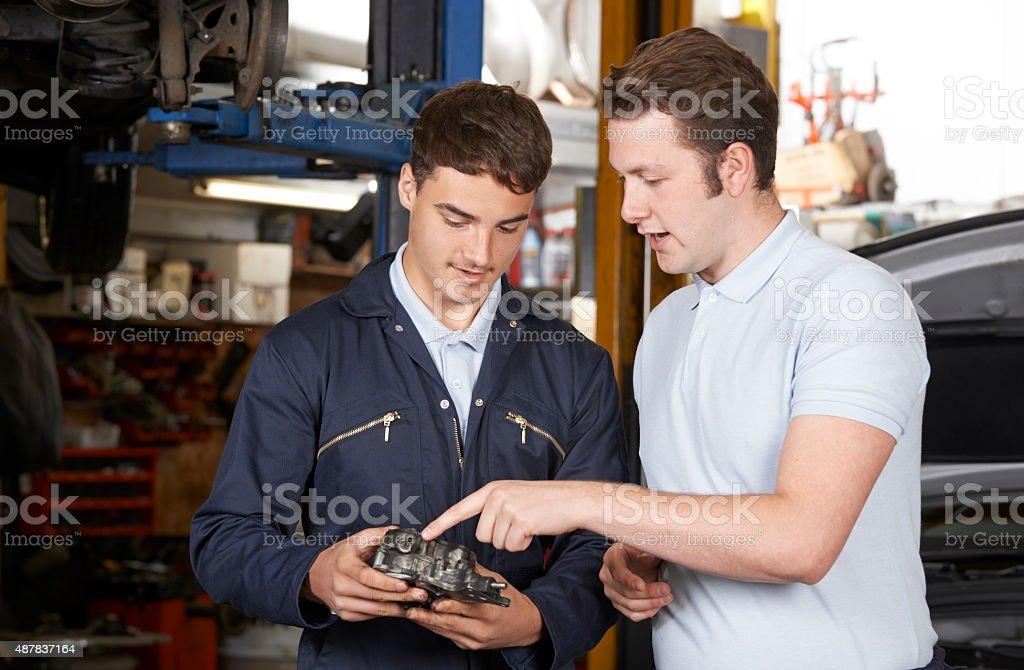 Mechanic Helping Apprentice To Fix Engine stock photo