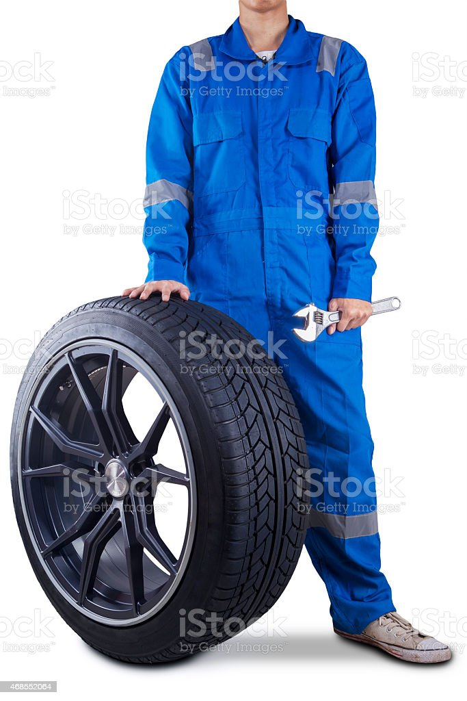 Mechanic holding a tire and wrench stock photo