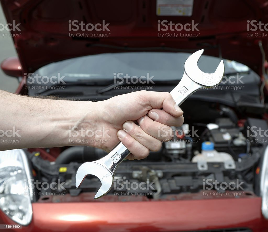 Mechanic holding spanner with car royalty-free stock photo