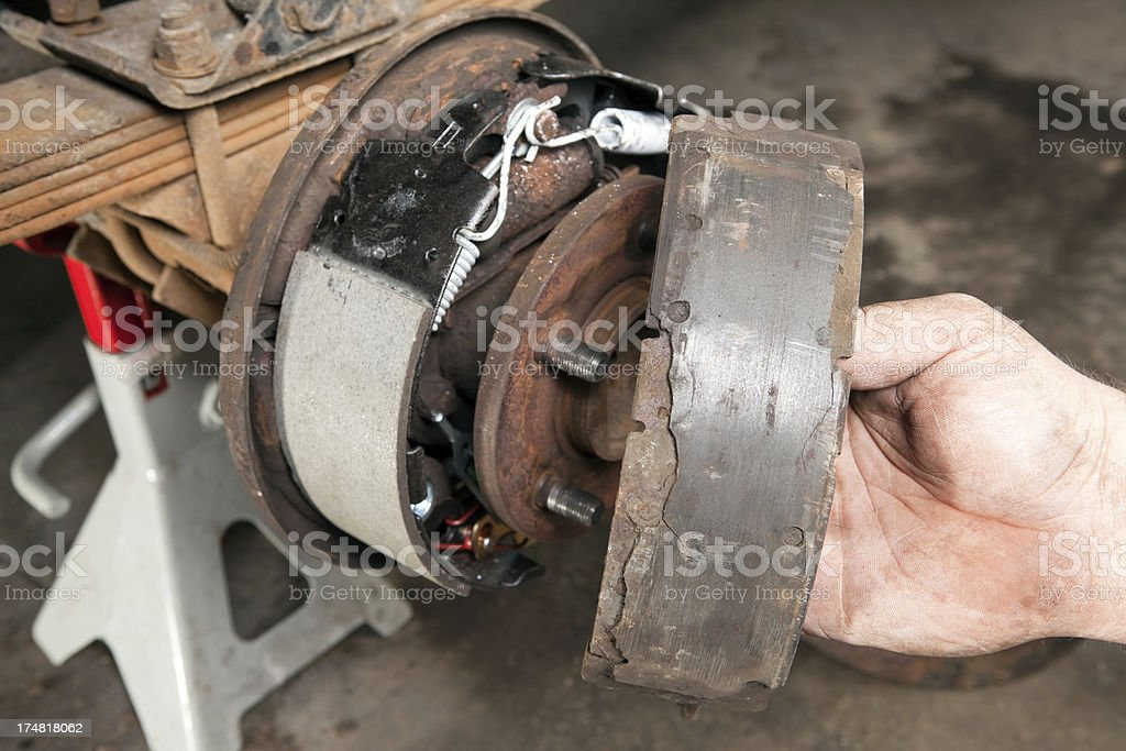 Mechanic Holds Old Brake Pad near New royalty-free stock photo