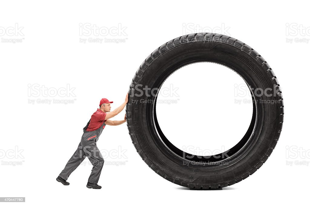 Mechanic in a gray jumpsuit pushing a giant black tire stock photo