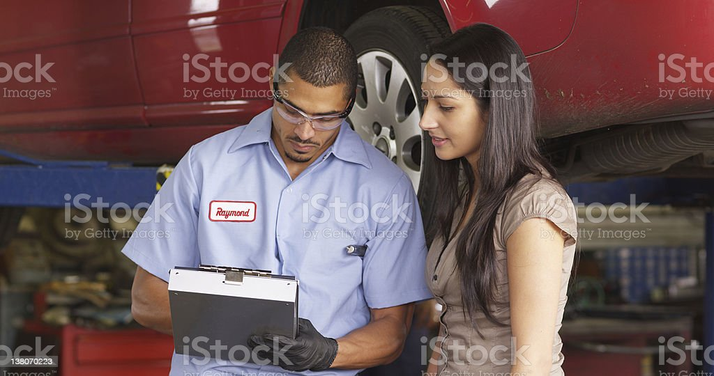 Mechanic in auto repair shop works with customer stock photo