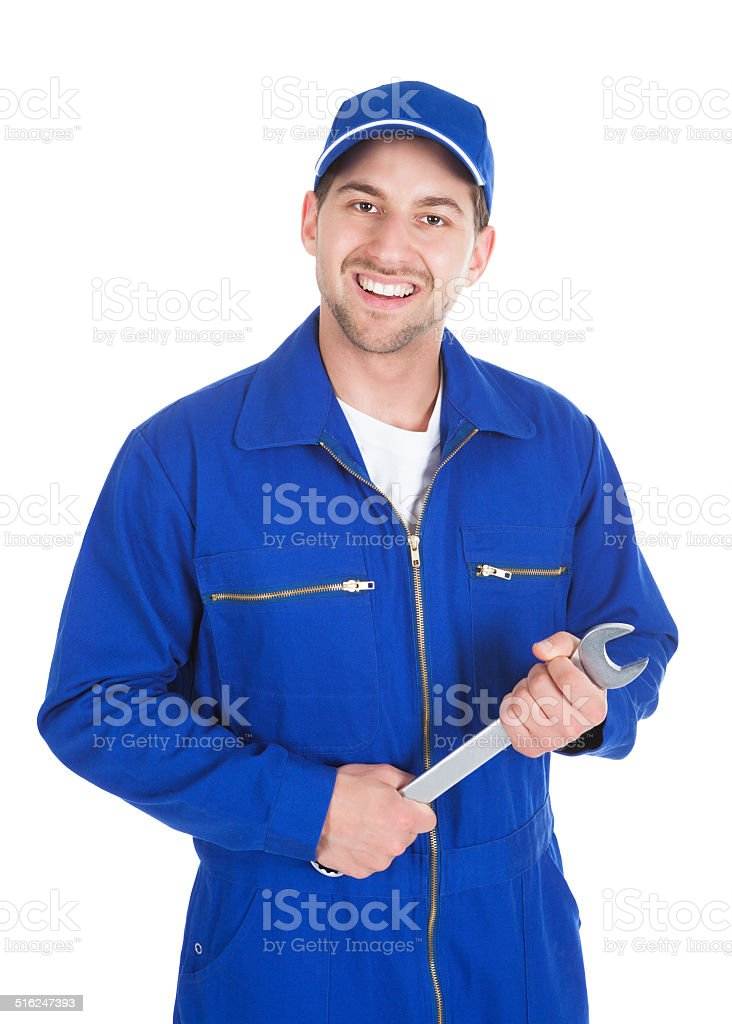 Mechanic In Blue Overalls Holding Spanner stock photo