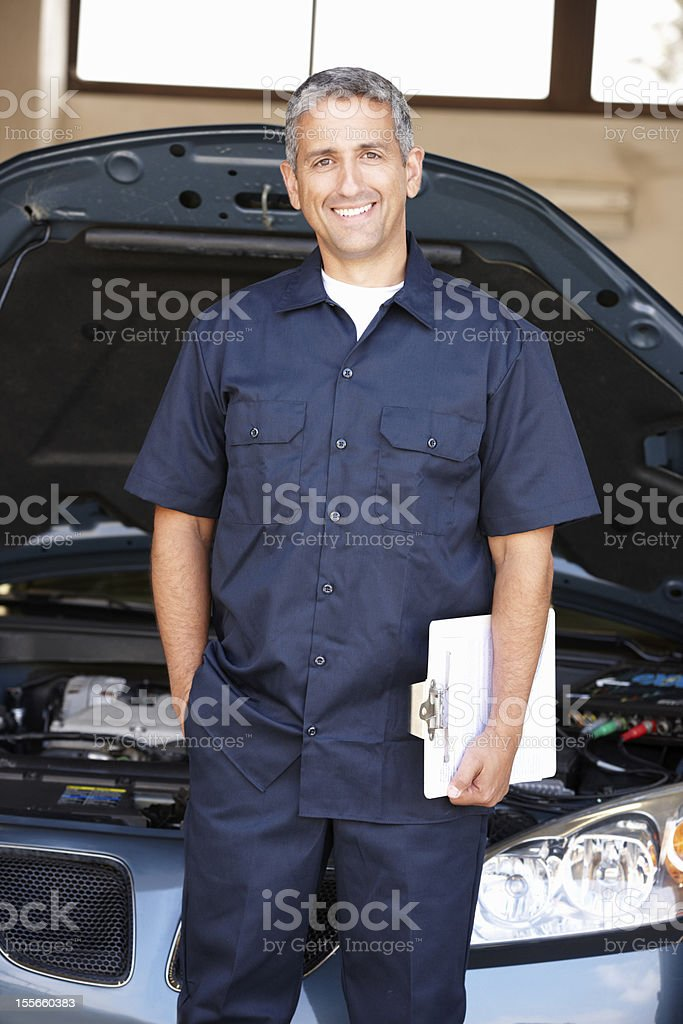 Mechanic in front of a car with a clipboard royalty-free stock photo