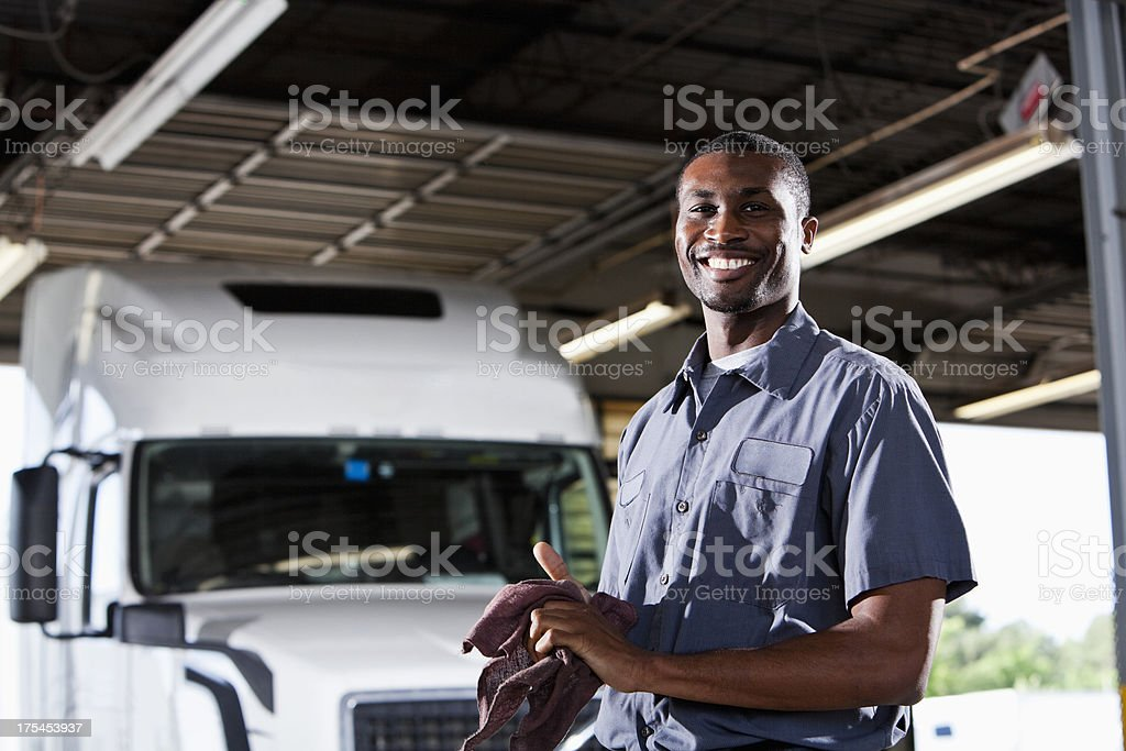 Mechanic in garage with semi-truck stock photo