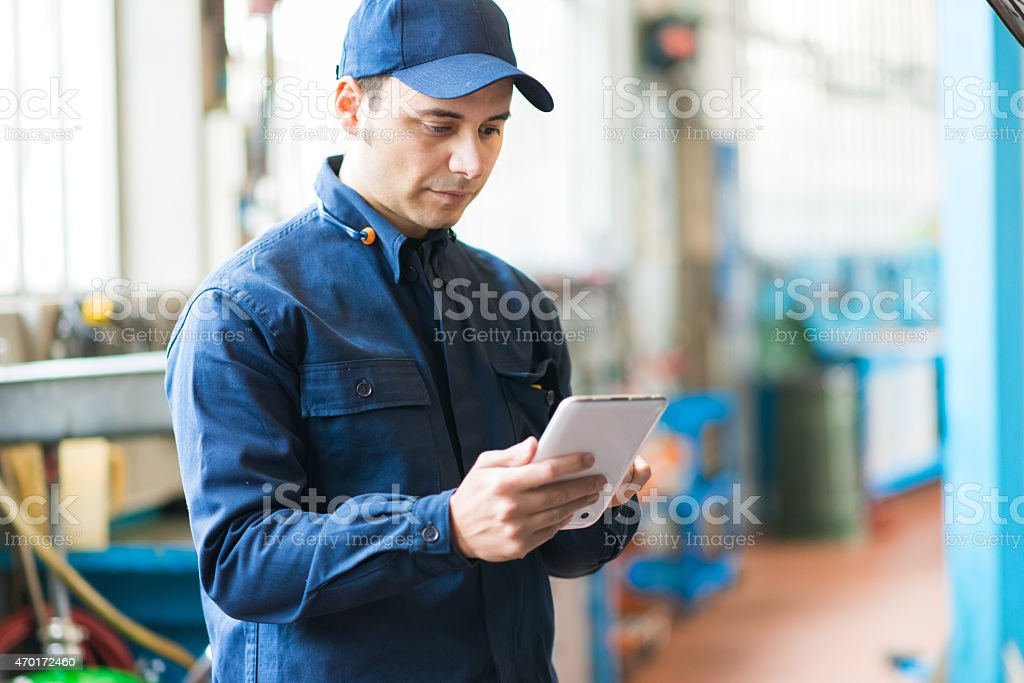 A mechanic in his garage focusing on his upside down tablet stock photo