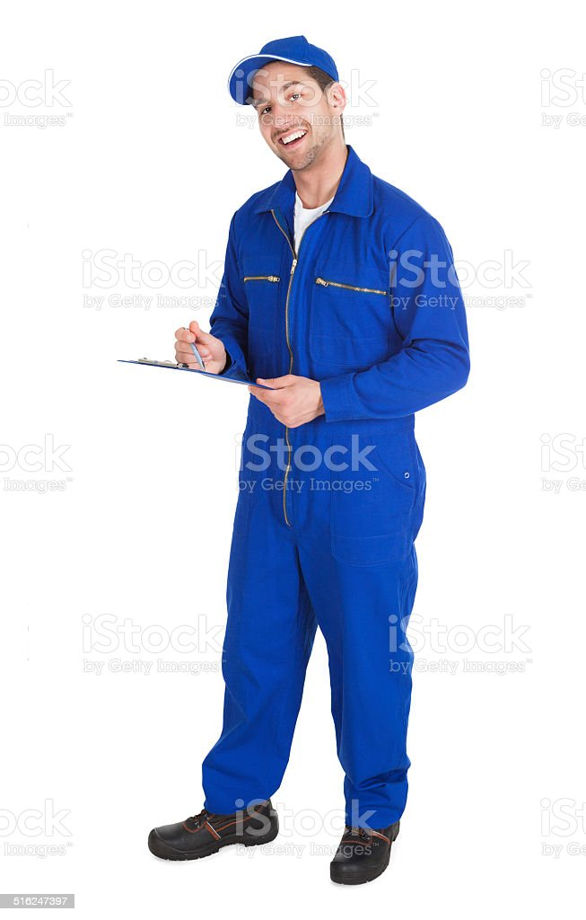Mechanic In Overall Writing On Clipboard stock photo