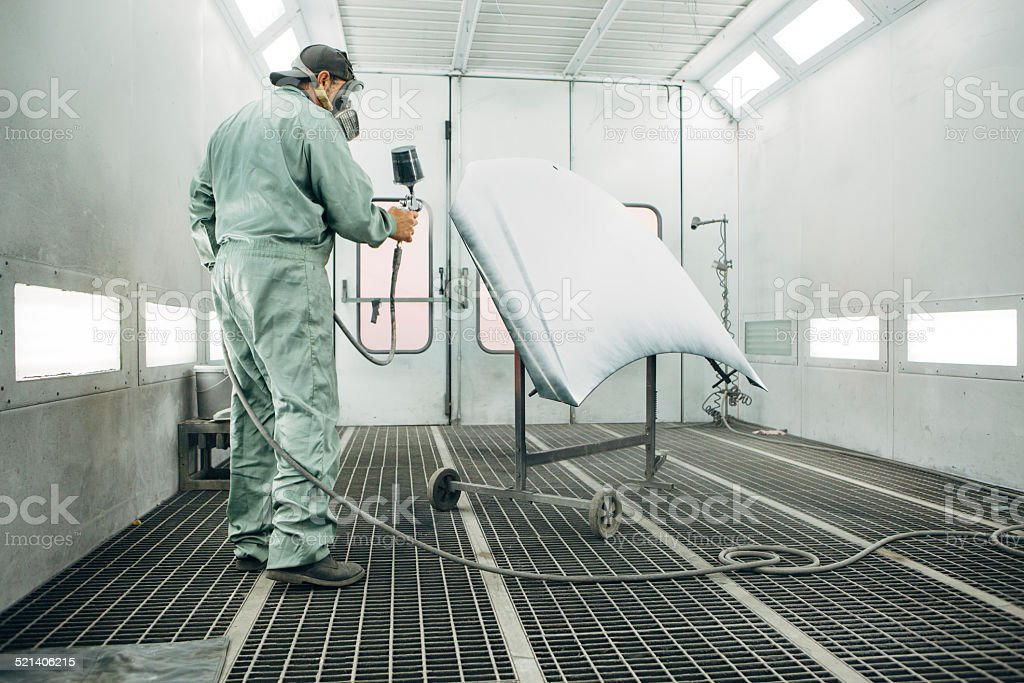 mechanic in Painting Booth spray the hood of a car stock photo