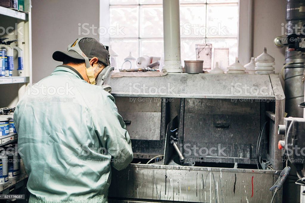 mechanic in protective workwear mixes colors for airbrush stock photo