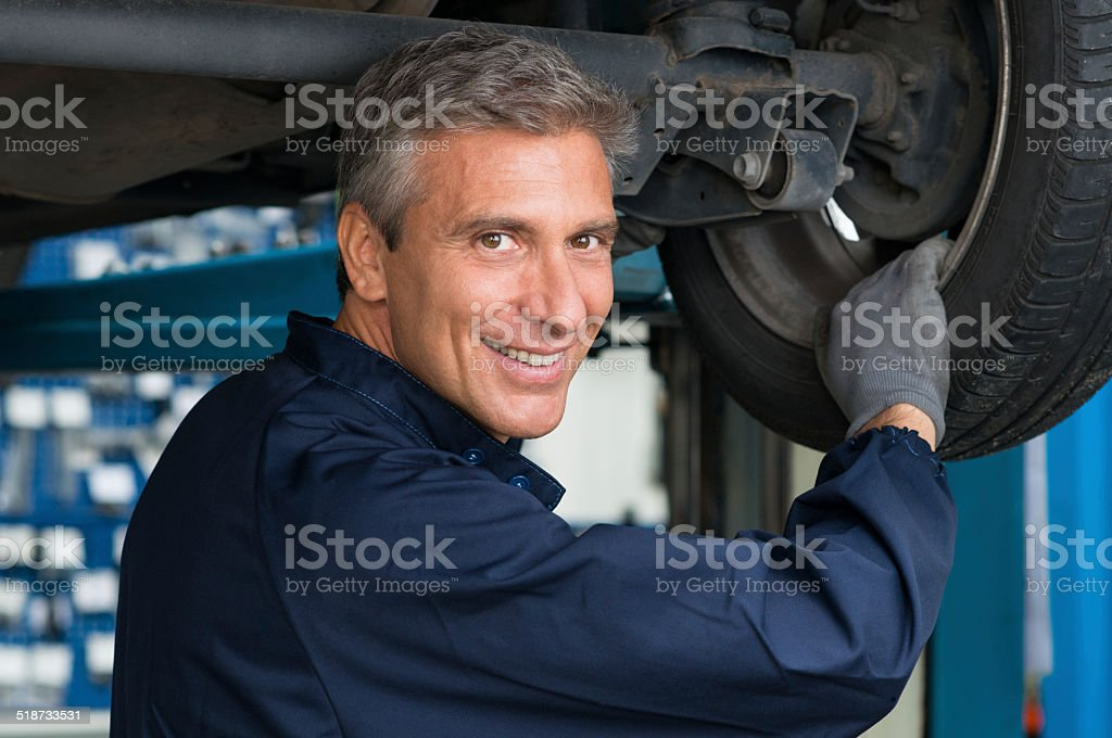 Mechanic In Workshop Changing Tire stock photo