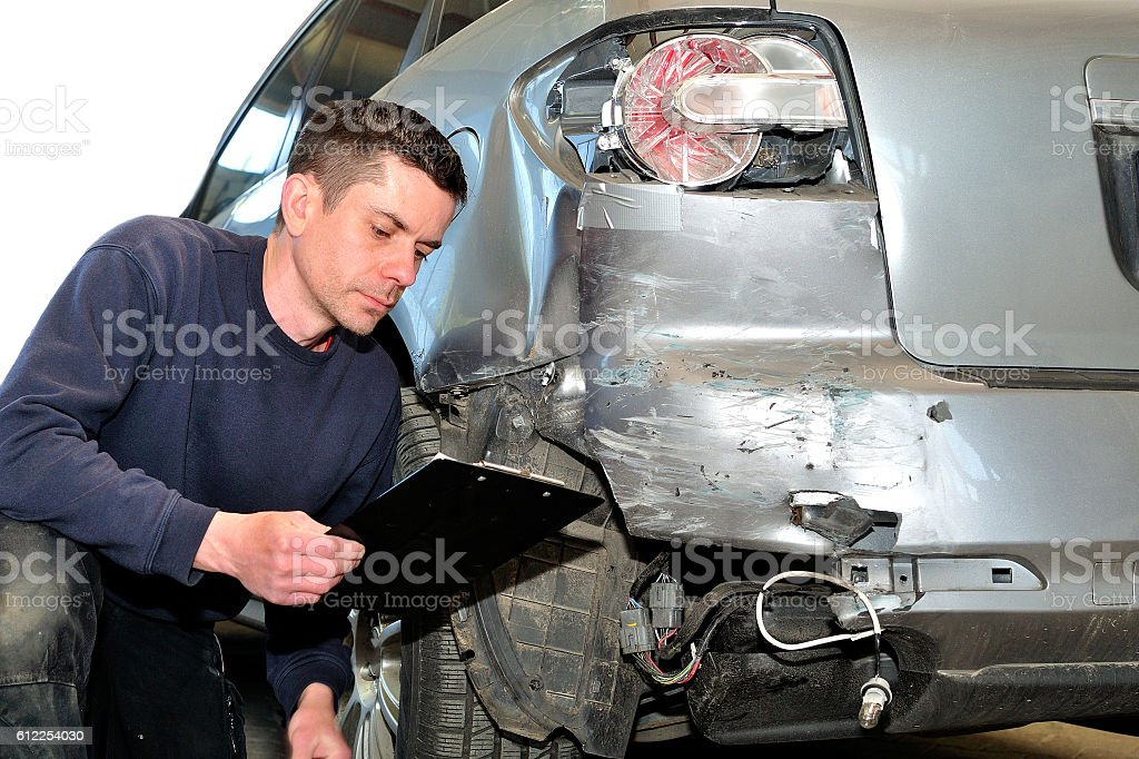 Mechanic inspecting car body at auto repair shop service station stock photo