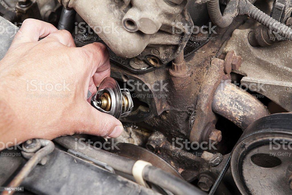 Mechanic Installing Thermostat into Engine Block royalty-free stock photo