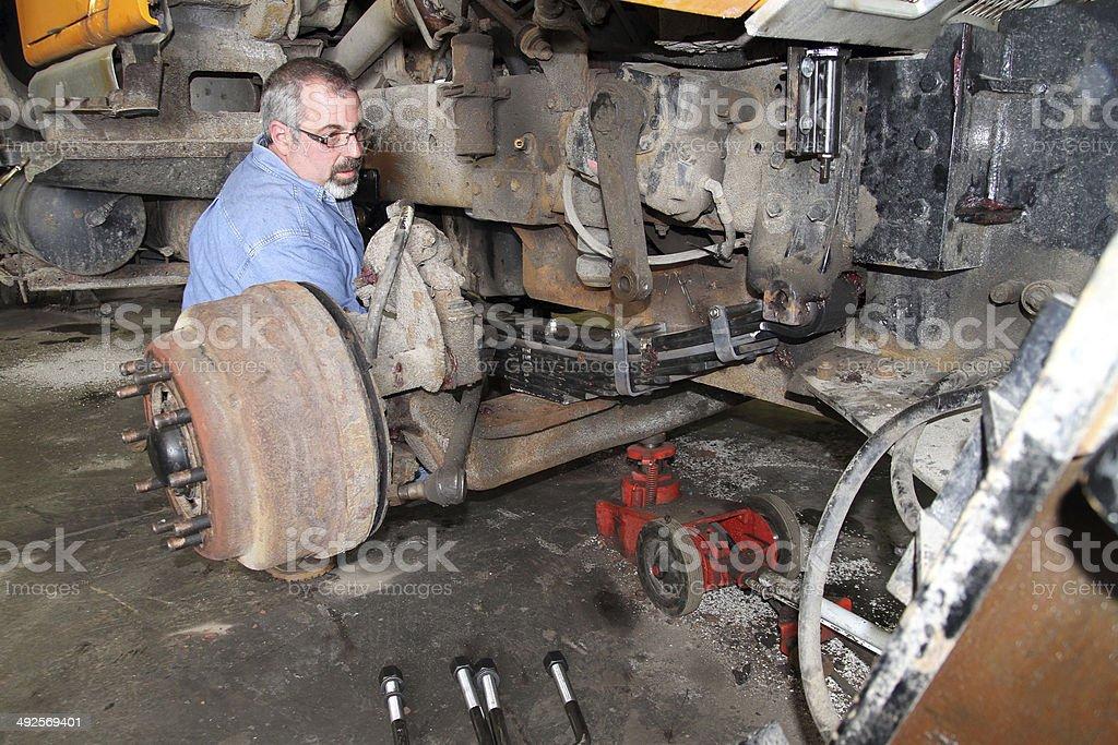 Mechanic installs leaf spring on heavy truck stock photo