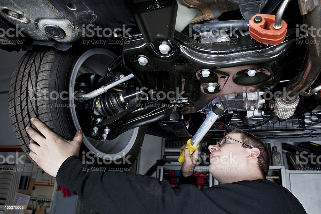 Mechanic is checking the shock absorbers of a modern car stock photo