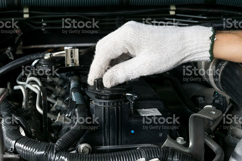 mechanic is opening the oil cap from a car engine. stock photo