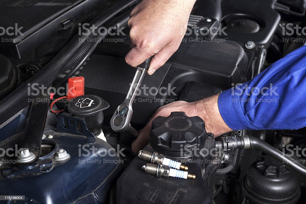 Mechanic is unscrewing the ignition plugs of a modern car stock photo