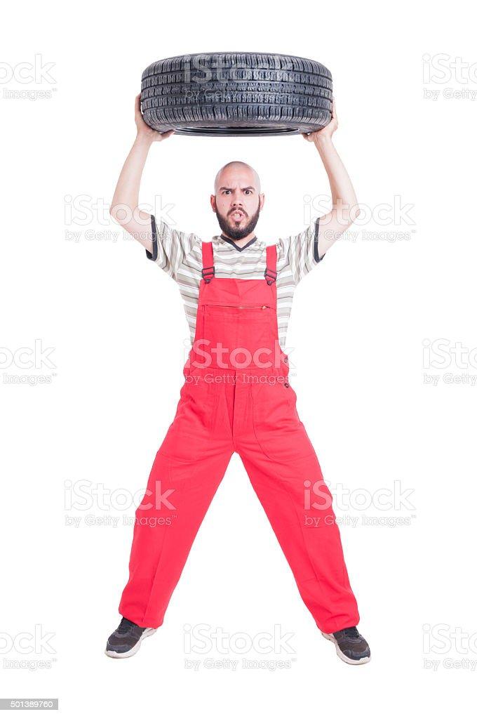 Mechanic lifting a car wheel above head stock photo